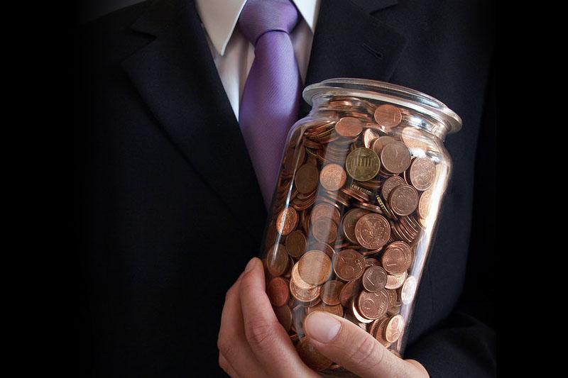 Mann hält ein Glas mit Cent-Münzen in der Hand